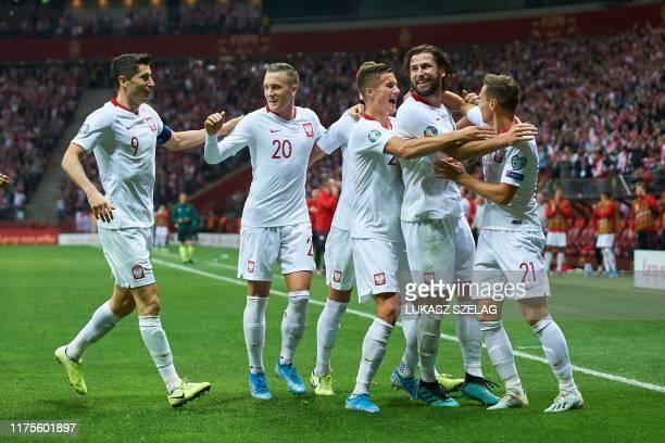 Poland's forward Robert Lewandowski and teammates celebrate the opening goal by Poland's midfielder Przemyslaw Frankowski celebrates scoring during...