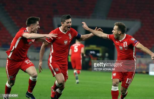 Poland's forward Robert Lewandowski celebrates scoring with his team-mates during the FIFA World Cup Qatar 2022 qualification football match Hungary...