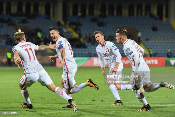 Poland's forward Robert Lewandowski celebrates with teammates after scoring the team's third goal from a free kick during the FIFA World Cup 2018...
