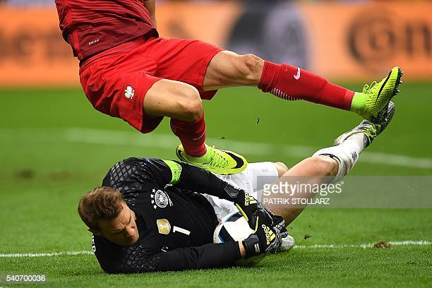 Poland's forward Robert Lewandowski challenges Germany's goalkeeper Manuel Neuer during the Euro 2016 group C football match between Germany and...