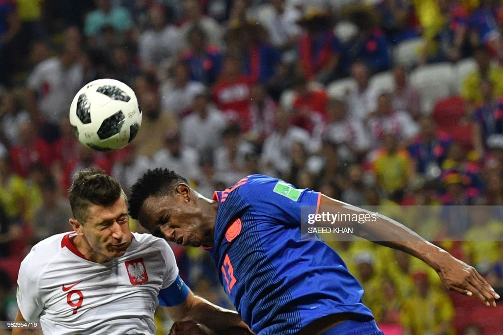 TOPSHOT - Poland's forward Robert Lewandowski (L) heads the ball with Colombia's defender Yerry Mina during the Russia 2018 World Cup Group H football match between Poland and Colombia at the Kazan Arena in Kazan on June 24, 2018. (Photo by SAEED KHAN / AFP) / RESTRICTED