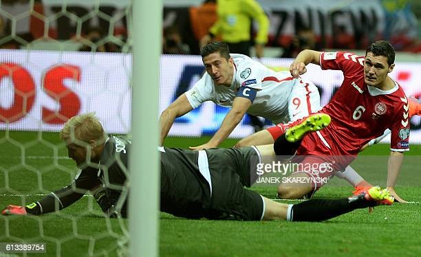 Poland's forward Robert Lewandowski scores a goal against Denmark's goalkeeper Kasper Schmeichel and Andreas Christensen during the 2018 World Cup...