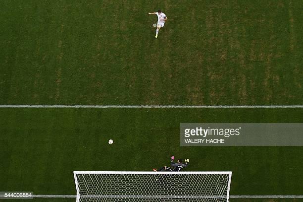 Poland's forward Robert Lewandowski shoots and scores in a penalty shootout during the Euro 2016 quarterfinal football match between Poland and...