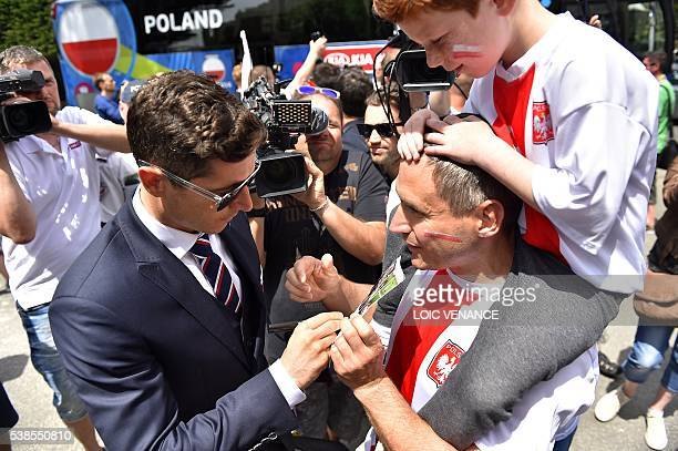 Poland's forward Robert Lewandowski signs autographs as he arrives with teammates at the Hermitage hotel in La Baule on June 7 three days prior to...