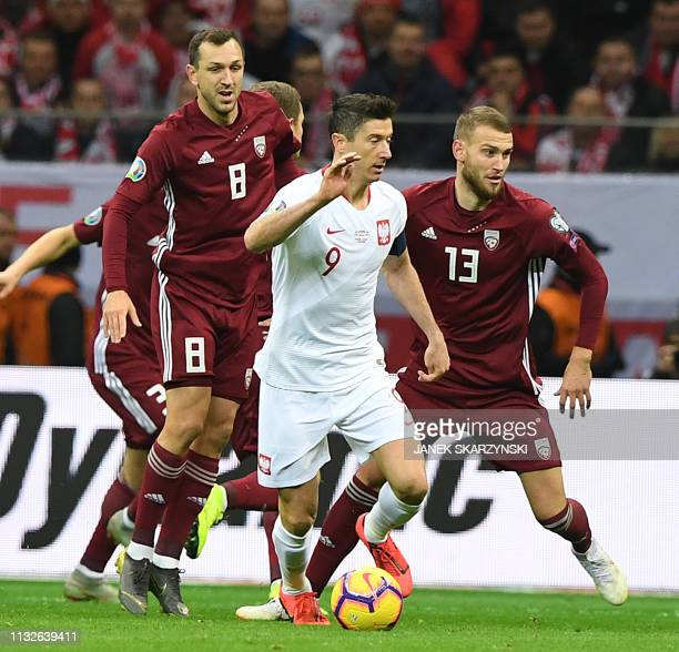 Poland's forward Robert Lewandowski vies for the ball with Latvia's midfielder Olegs Laizans and Latvia's defender Vjaceslavs Isajevs during the UEFA...