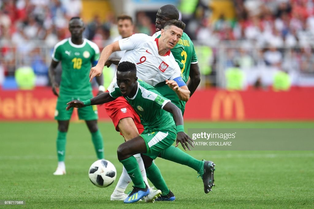TOPSHOT - Poland's forward Robert Lewandowski (C) vies with Senegal's defender Kalidou Koulibaly (BACK) and Senegal's midfielder Idrissa Gana Gueye the Russia 2018 World Cup Group H football match between Poland and Senegal at the Spartak Stadium in Moscow on June 19, 2018. (Photo by Patrik STOLLARZ / AFP) / RESTRICTED