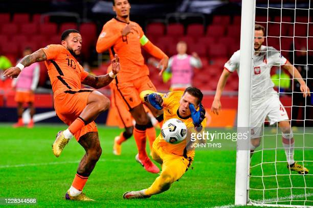 Poland's goal keeper Bartlomiej Dragowski stops the ball in front of Dutch's forward Memphis Depay during the UEFA Nations League football match...