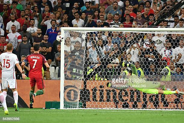 TOPSHOT Poland's goalkeeper Lukasz Fabianski dives for the ball next to Portugal's forward Cristiano Ronaldo during the Euro 2016 quarterfinal...