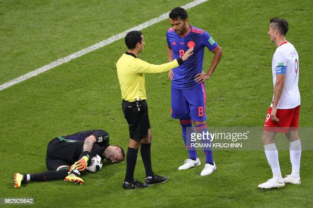 Poland's goalkeeper Wojciech Szczesny lies on the pitch as Mexican referee Cesar Ramos talks to Colombia's midfielder Abel Aguilar during the Russia...