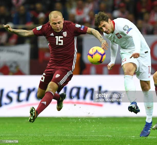 Poland's Grzegorz Krychowiak vies for the ball with Latvia's Deniss Rakels during the UEFA Euro 2020 Group B qualification football match between...