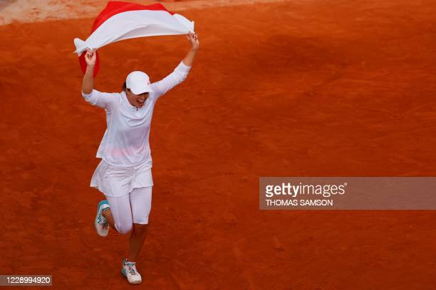Poland's Iga Swiatek celebrates with the Polish national flag after winning against Sofia Kenin of the US during their women's singles final tennis...