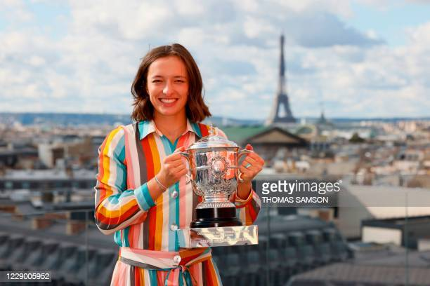 Poland's Iga Swiatek poses with the trophy Suzanne Lenglen near the Eiffel Tower in Paris, on October 11, 2020 a day after winning The Roland Garros...