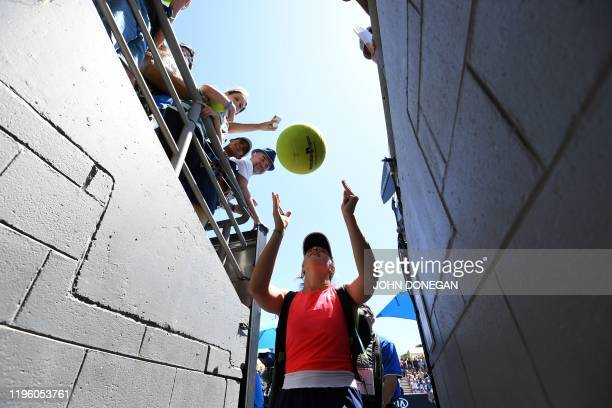 Poland's Iga Swiatek signs autographs after her women's singles match against Croatia's Donna Vekic on day six of the Australian Open tennis...