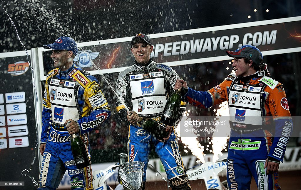 Poland's Jaroslaw Hampel (C) celebrates with champaign after winning the Danish Speedway Grand Prix on the podium with second placed Tomasz Gollob of Poland (L) and third placed Chris Harris from Great Britain at Parken Stadium on June 5, 2010 in Copenhagen.