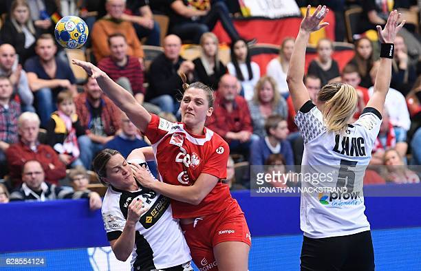 Poland's Joanna Drabik and Germany's Anna Loerper vie for the ball during the Women's European Handball Championship Group B match between Germany...