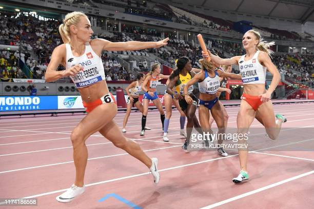 TOPSHOT Poland's Justyna SwietyErsetic receives the baton from Poland's Malgorzata HolubKowalik in the Women's 4x400m Relay final at the 2019 IAAF...