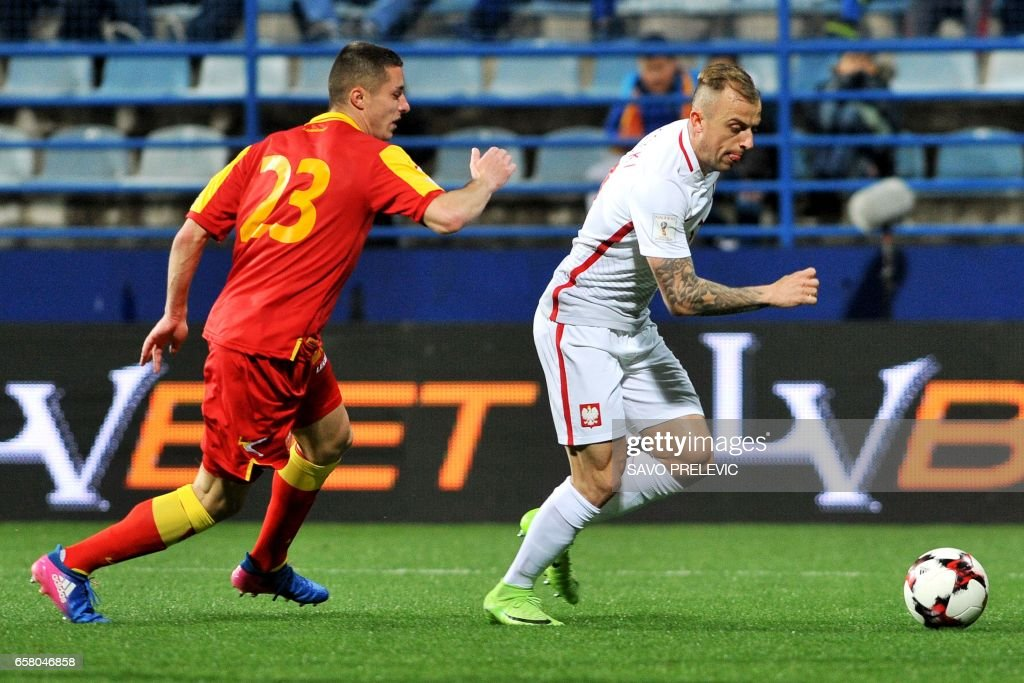 Poland's Kamil Grosicki (R) vies with Montenegro's Adam Marusic during the FIFA World Cup 2018 qualification football match between Montenegro and Poland in Podgorica on March 26, 2017. /