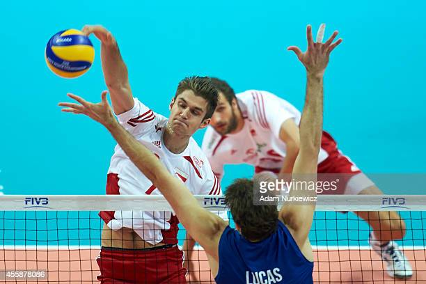 Poland's Karol Klos spikes the ball against Brazil's Lucas Saatkamp during the FIVB World Championships Final match between Brazil and Poland at...