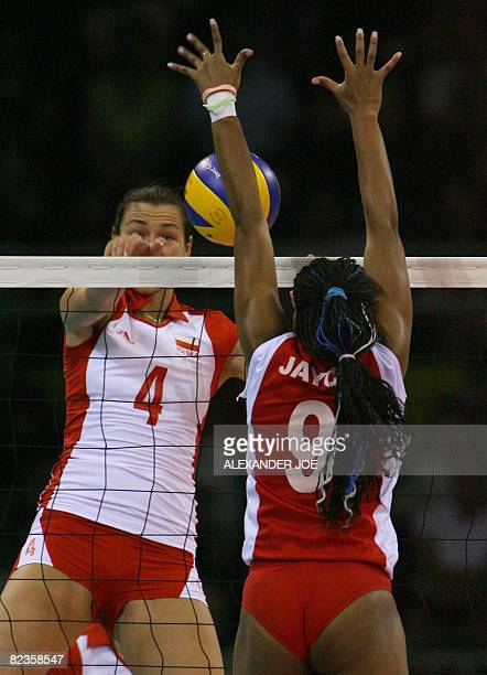 Poland's Katarzyna Gajgal slams a shot onto Venezuelas Jayce Andrade Andrade during a Preliminary Olympic Volleyball Pool A match 21 at the Capital...
