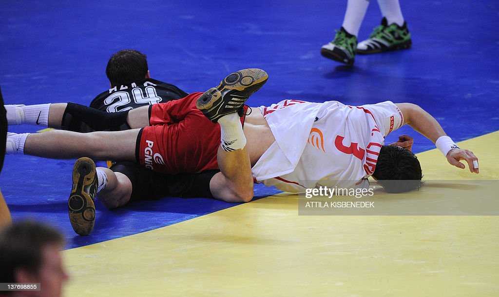 Poland's Krzysztof Lijewski (R) falls on Germany's Michael Hass (L) during the Men's EHF Euro 2012 Handball Championship match Poland vs Germany on January 25, 2012 at the Belgrade Arena.