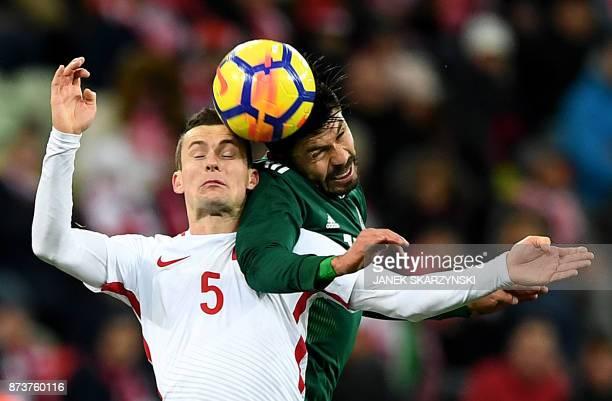 TOPSHOT Poland's Krzysztof Maczynski and Mexico's Oribe Peralta vie for the ball during the friendly football match Poland v Mexico at the Ergo Arena...