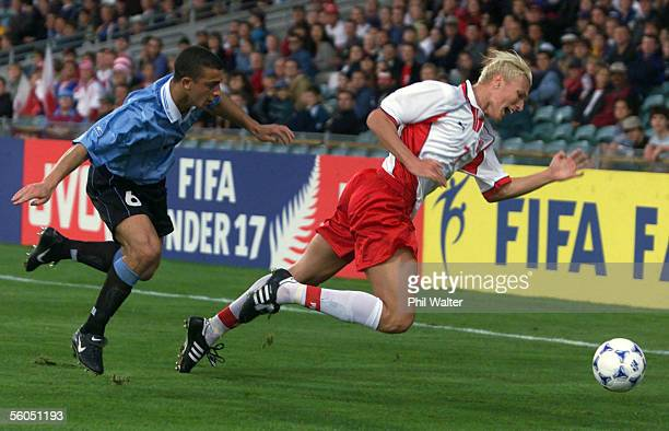 Poland's Lukasz Nawotczynski trips along with Uruguay's Miguel Lapolla as they both try for the ball during their match in the U17 World Soccer...