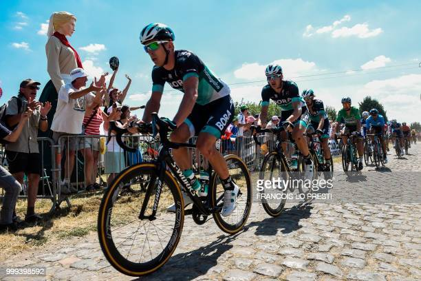 Poland's Maciej Bodnar rides with the pack through the stage's first cobblestone section in Thunl'Eveque during the ninth stage of the 105th edition...
