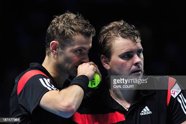 Poland's Marcin Matkowski and his partner Poland's Mariusz Fyrstenberg talk between points against US player Bob Bryan and his partner US player Mike...