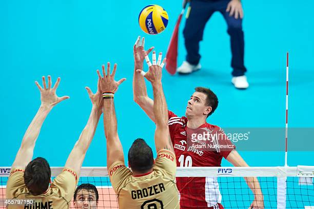 Poland's Mariusz Wlazly attacks against Germany's Marcus Boehme and Gyorgy Grozer during the FIVB World Championships SemiFinal match between Germany...