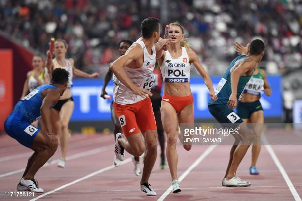 Poland's Matgorzata HolubKowalik passes the baton to Rafal Omelko in the Mixed 4 x 400m Relay heats at the 2019 IAAF World Athletics Championships at...