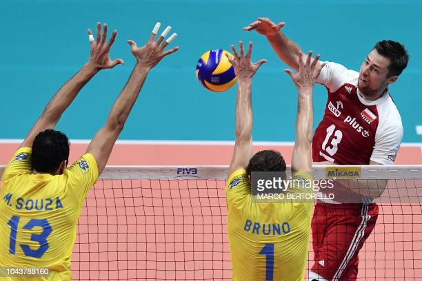 TOPSHOT Poland's Michal Kubiak hits the ball as Brazil's Mauricio Souza and Brazil's Bruno Mossa Rezende try to block during the 2018 FIVB World...