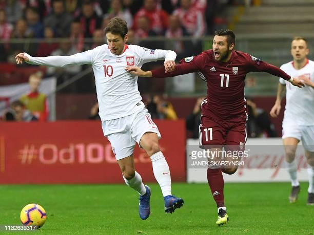 Poland's midfielder Grzegorz Krychowiak vie for the ball with Latvia's forward Arturs Karasauskas during the UEFA Euro 2020 football Groupe G...