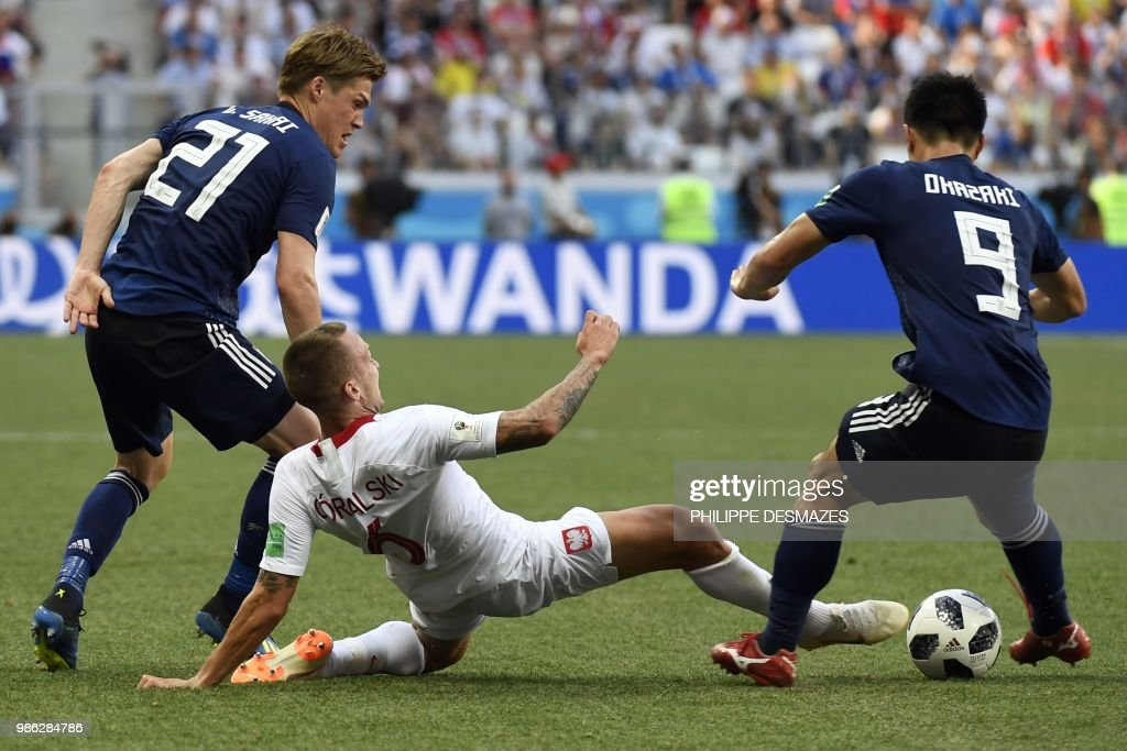 Poland's midfielder Jacek Goralski (C) vies with Japan's defender Gotoku Sakai (L) and Japan's forward Shinji Okazaki during the Russia 2018 World Cup Group H football match between Japan and Poland at the Volgograd Arena in Volgograd on June 28, 2018. (Photo by Philippe DESMAZES / AFP) / RESTRICTED