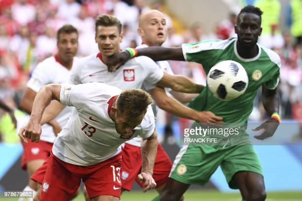TOPSHOT Poland's midfielder Maciej Rybus heads the ball next to Poland's defender Lukasz Piszczek and Senegal's defender Salif Sane during the Russia...