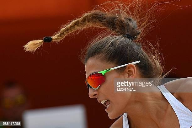 Poland's Monika Brzostek is seen as she and teammate Kinga Kolosinska return the ball to Brazil's Larissa Franca Maestrini and Talita Rocha during...
