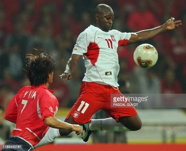 Poland's Nigerian-born forward Emmanuel Olisadebe vies for the ball with South Korea's Kim Tae Young , 04 June 2002 at the Busan Asiad Main Stadium...