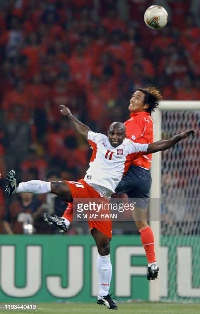 Poland's Nigerian-born forward Emmanuel Olisadebe vies for the ball with South Korea's Kim Tae-Young , 04 June 2002 at the Busan Asiad Main Stadium...