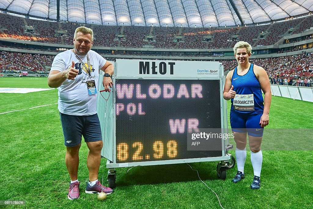 Poland's Olympic champion Anita Wlodarczyk poses with her coach Krzysztof Kliszewski next to a display showing her new world record in the Women's Hammer Throw during the athletics meeting of Kamila Skolimowska at the National Stadium in Warsaw, Poland, on August 28, 2016. Anita Wlodarczyk broke her own world record in the hammer with a throw of 82.98 metres in Warsaw. / AFP / Adam Nurkiewicz