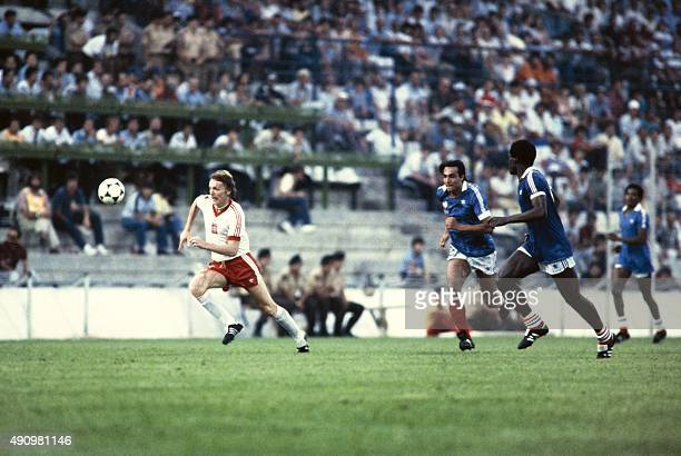 Poland's player runs with the ball next to French midfielder JeanFrancois Larios during the 1982 World Cup football match between Poland and France...