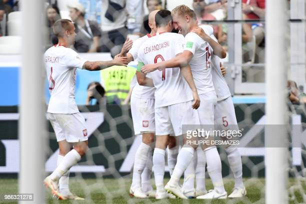 Poland's players celebrate after scoring the opener during the Russia 2018 World Cup Group H football match between Japan and Poland at the Volgograd...