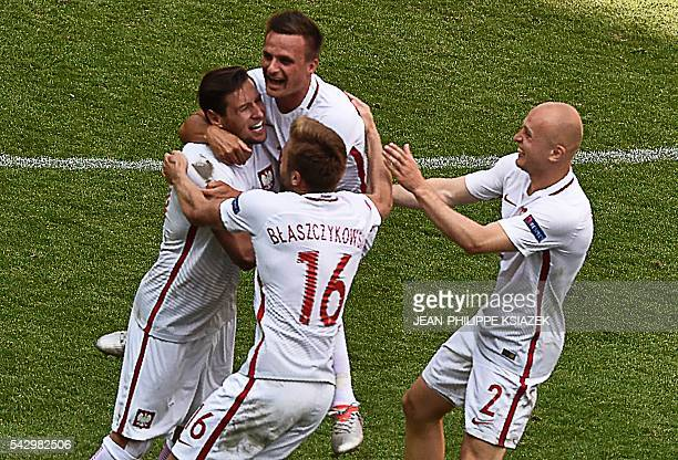 Poland's players celebrate after winning the penalty shootout during the Euro 2016 round of sixteen football match Switzerland vs Poland on June 25...