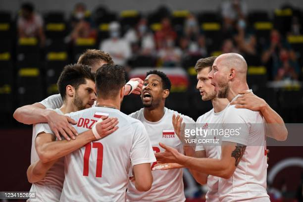 Poland's players react after a point in the men's preliminary round pool A volleyball match between Poland and Iran during the Tokyo 2020 Olympic...