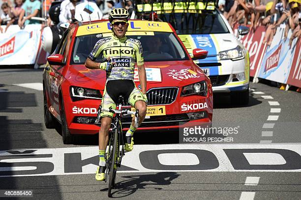Poland's Rafal Majka shows his team's logo as he celebrates at the finish line at the end of the 188 km eleventh stage of the 102nd edition of the...