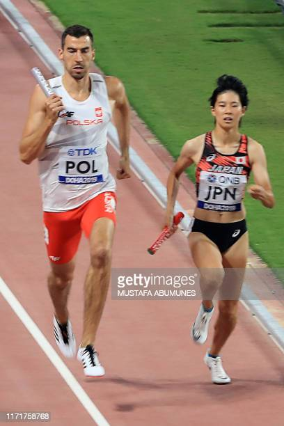 Poland's Rafal Omelko runs beside Japan's Saki Takashima in the final leg of the Mixed 4 x 400m Relay heats at the 2019 IAAF World Athletics...
