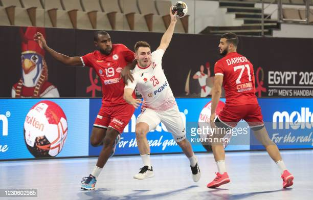 Poland's right back Arkadiusz Moryto is challenged by Qatar's right winger Marwane Sassi during the 2021 World Men's Handball Championship match...