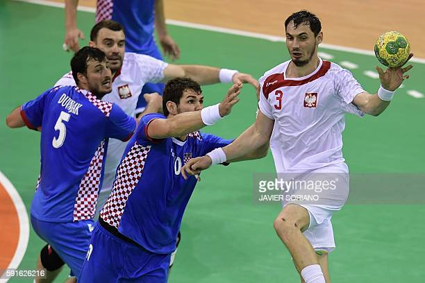 Poland's right back Krzysztof Lijewski passes the ball past Croatia's centre back Domagoj Duvnjak during the men's quarterfinal handball match...