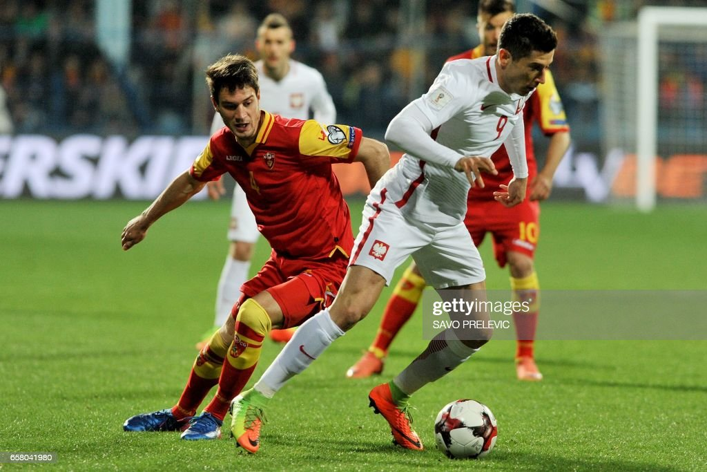 Poland's Robert Lewandowski (R) vies with Montenegro's Nikola Vukcevic during the FIFA World Cup 2018 qualification football match between Montenegro and Poland in Podgorica on March 26, 2017. /