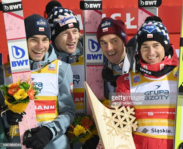 Poland's team Jakub Wolny Dawid Kubacki Piotr Zyla and Kamil Stoch celebrate on the podium after the team event of the FIS Ski Jumping World Cup in...