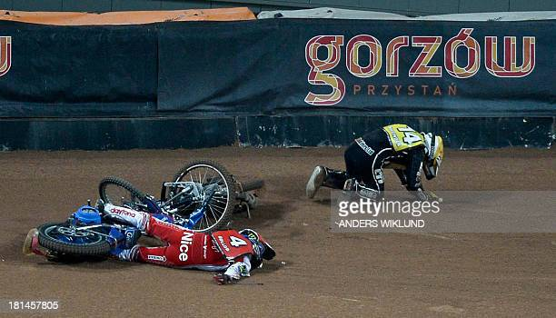 Poland's Tomasz Gollob lies on the track while Great Britain's Tai Woffinden tries to get up after a collision between the two drivers during the...