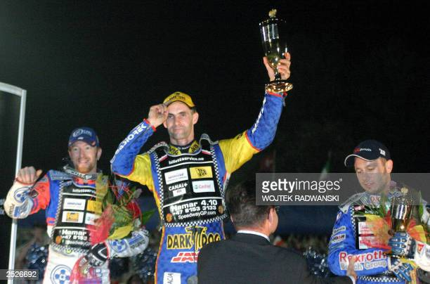 Poland's Tomasz Gollob who won the event Australian second placed Jason Crump and third placed Nicki Pedersen display their trophies on the podium of...